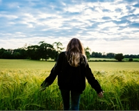 a person with long hair stands infront of a field
